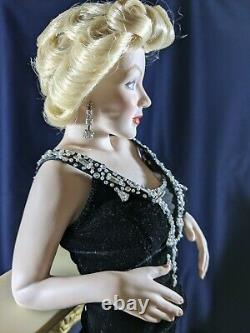 Franklin Mint Marilyn Monroe porcelain doll standing against a Fireplace